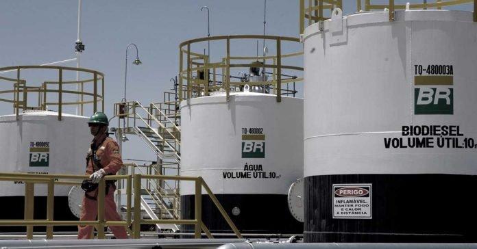 Na foto: um funcionário da Petrobrás com sua roupa de proteção. Ao fundo, plataformas de Biodiesel.