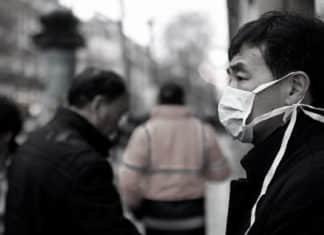 Imagem de um asiático com máscara, em função do coronavírus