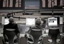 Operadores sentados em frente a tela de negociação, com as mãos na cabeça por causa do circuit breaker