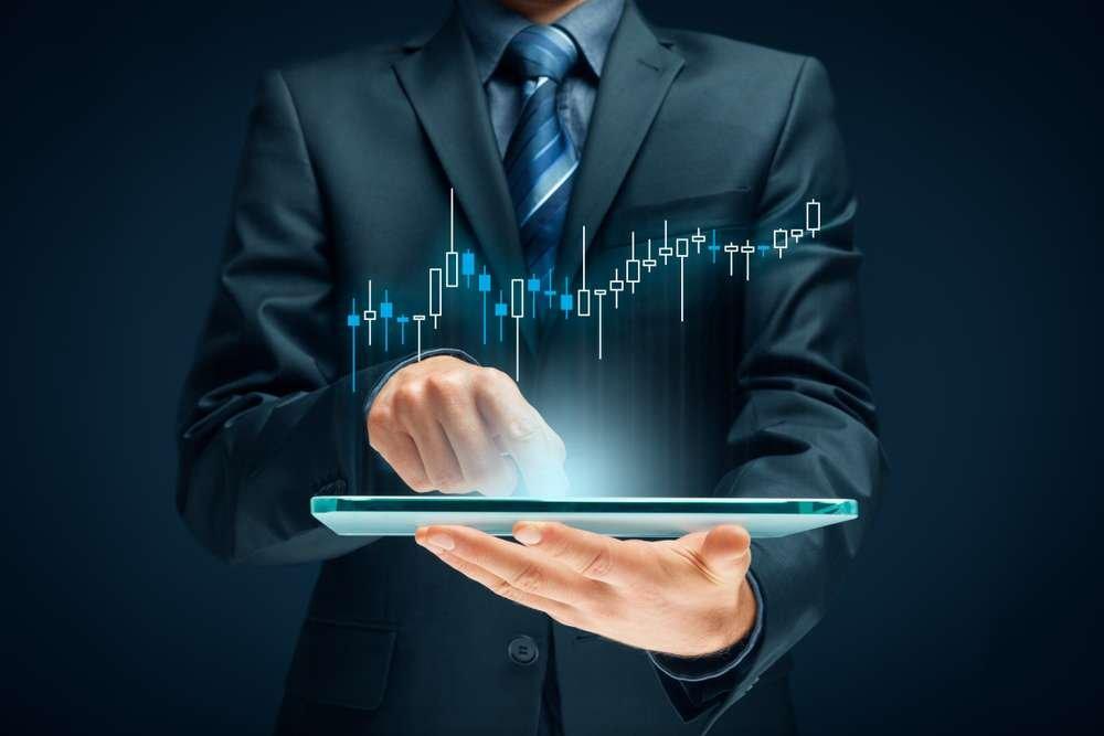 foto de um homem segurando um tablet com gráficos na cor verde água que simbolizam o COE